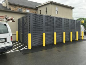 PalmSHIELD's horizontal louvered enclosure in a dark gray surrounds one said of Mission Dispensary and contrasts pleasingly with some bright yellow traffic columns to increase protection